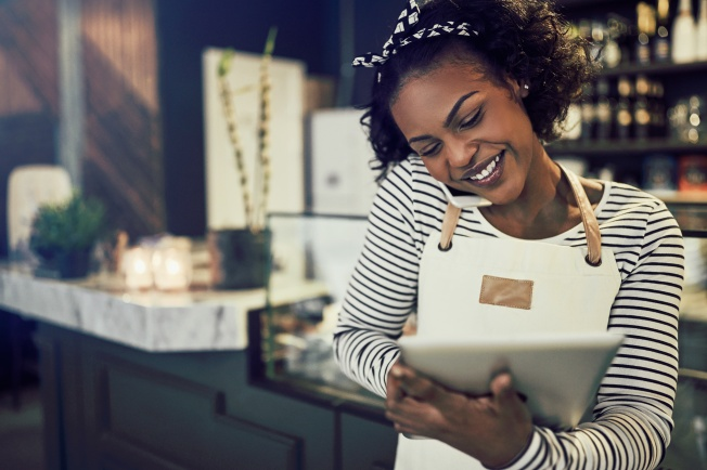 Femme au tablier dans un café au téléphone et utilisant une tablette
