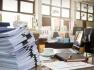 Bureau encombré sur lequel se trouve une grosse pile de feuilles de papier au premier plan