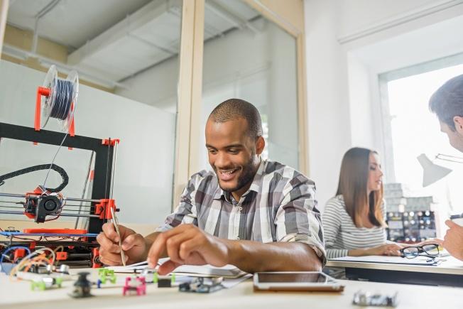 Homme avec bureau avec imprimante 3D