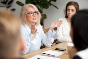 Une femme parle, assise à une table de réunion