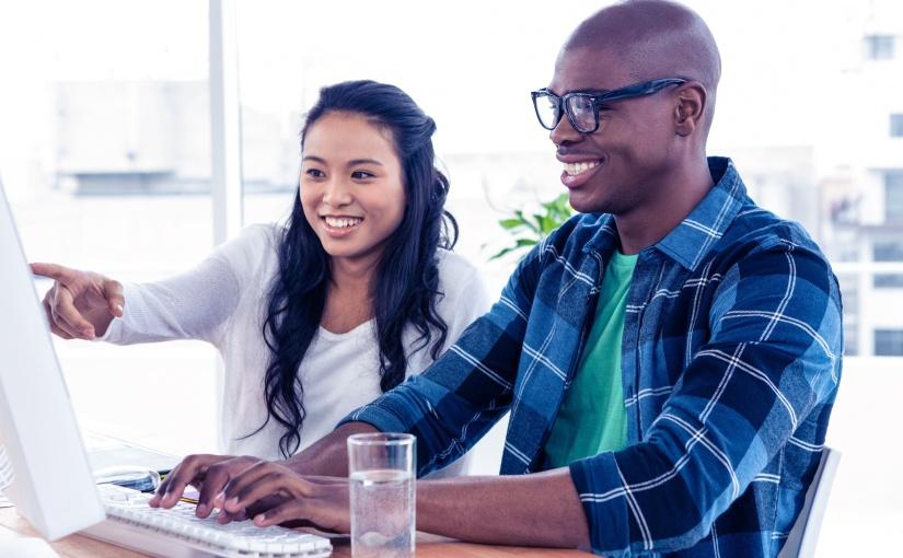Deux personnes assises devant un ordinateur de bureau