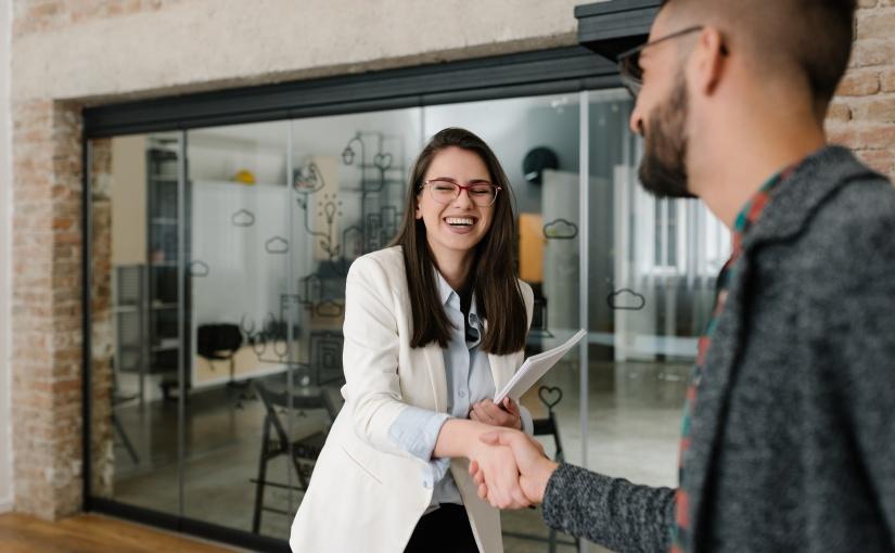 Deux personnes se serrant la main devant un bureau.