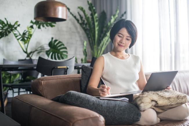 Femme sur un divan munie d'un ordinateur portable