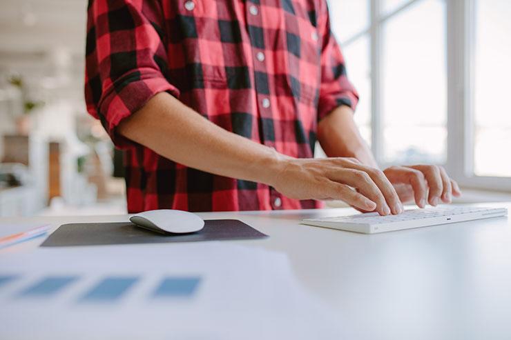 Compétences et qualités d'un professionnel de l'administration : mains masculines tapant sur un clavier d'ordinateur