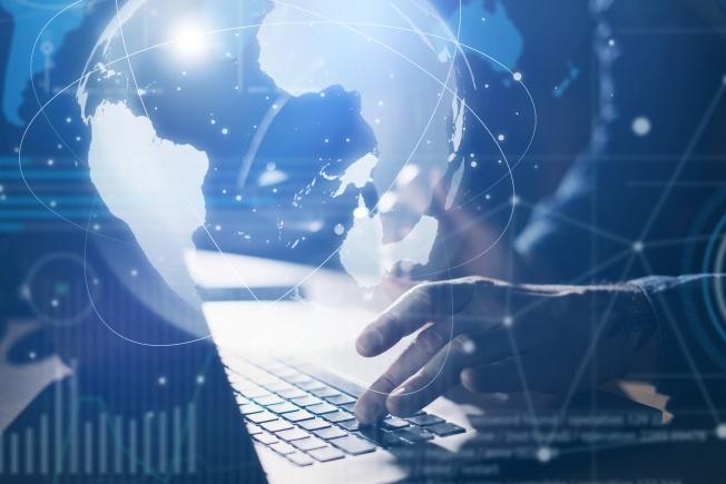 Mains d'une personne et ordinateur portable avec image superposée du globe