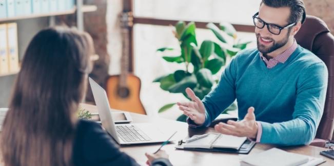 Préparation à l'entrevue – Homme d'affaires au travail, assis à un bureau, qui pose des questions à un candidat; jeune fille qui prend des notes.