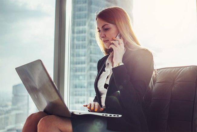 Jeune femme attendant assise dans le hall d'un bureau moderne : comment faire un suivi après une entrevue