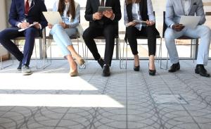 Cinq personnes assises attendent qu'on les appelle pour leur entrevue.