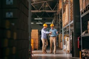 Des travailleurs circulant dans un entrepôt en pointant des boîtes : santé et sécurité au travail