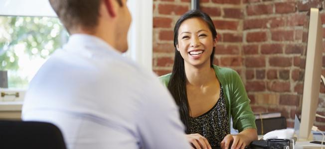 Femme souriante assise à son bureau et parlant à un homme.