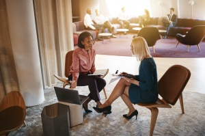 Négociation d'une offre d'emploi: deux femmes d'affaires discutant du travail sur un ordinateur portable dans un bureau
